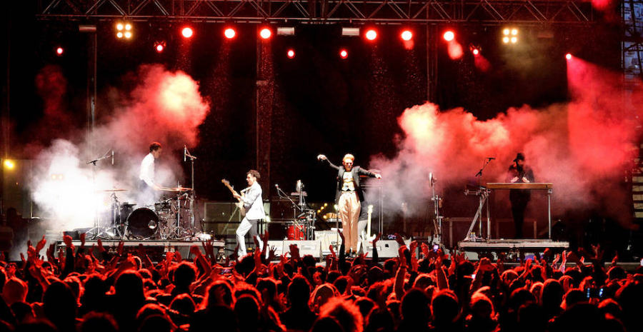 Image Showing A Rocking Performance of a pop singer with his musical band in a grand musical event.