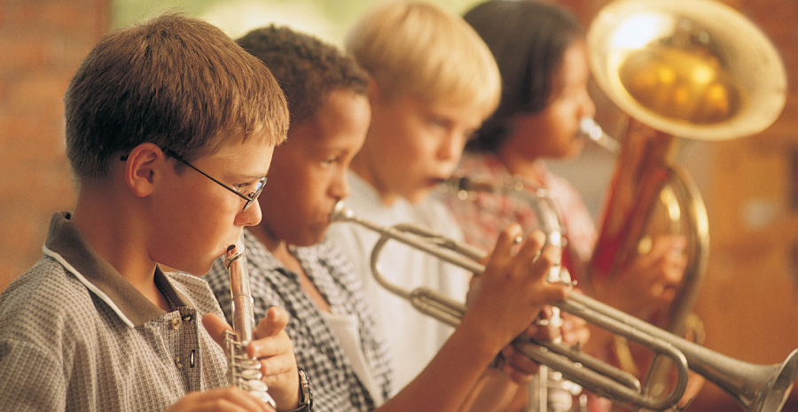 Group of Boys Playing Trumpet Instrument During A Musical Performance.
