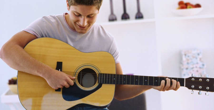 A Teenage Boy Playing his acoustic guitar.