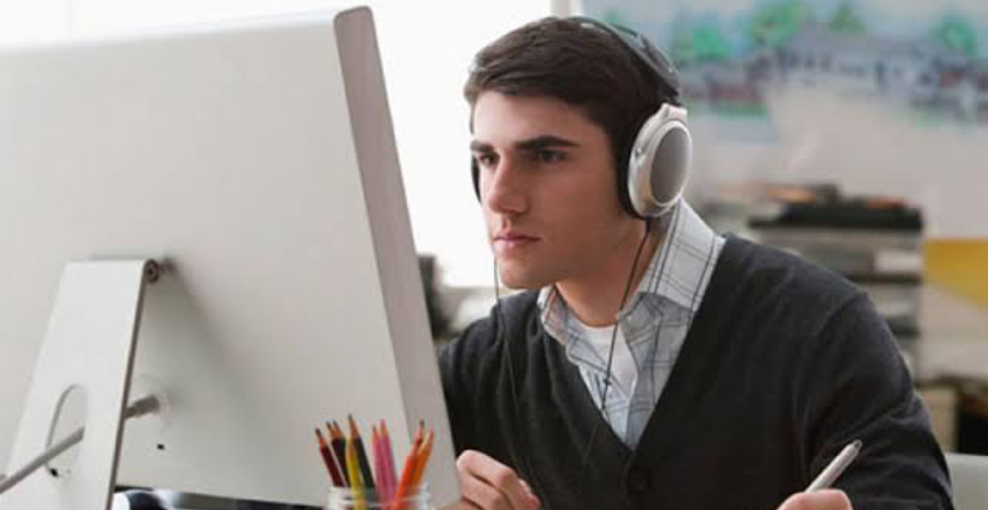 Casually Dressed Young Designer Listening To Music On Headphones While Working On A Laptop At A Desk In An Office