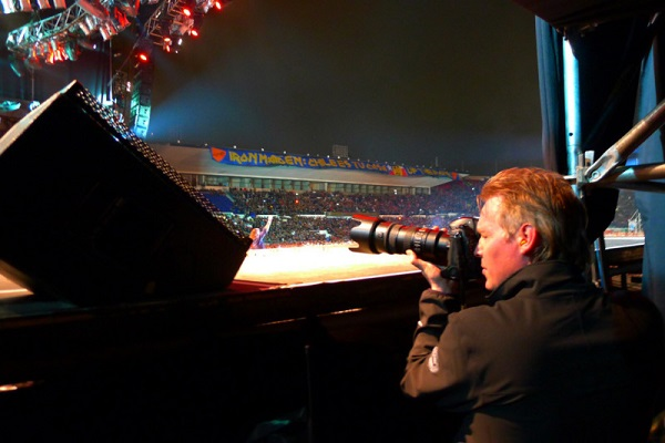 Image Featuring A Professional Event Photographer Taking Photos Of A Musical Concert.