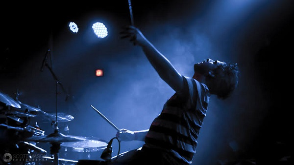 An Image Of Male Lead Drummer Enjoying His Performance On The Stage.